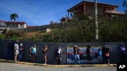 Sejumlah orang antre di luar SD Maria Simmons, untuk vaksinasi COVID-19 di Vieques, Puerto Rico, 10 Maret 2021.