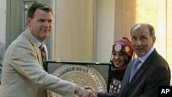 Canada's Foreign Minister John Baird (L) exchanges gifts with the head of Libya's National Transitional Council Mustafa Abdel Jalil, during his first visit to the rebel-held city of Benghazi, June 27, 2011
