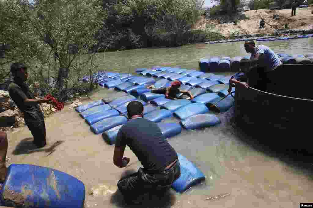 Krijumčari dizel goriva iz Turske u Siriju preko rijeke Al-Assi nedaleko od grada Darkush, nadajući se dobroj zaradi.