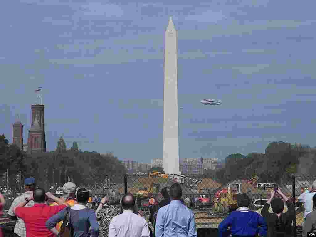 Residentes y turistas asisten al histórico momento cuando el Discovery vuela sobre la Alameda Nacional con el Monumento a Washington como testigo.