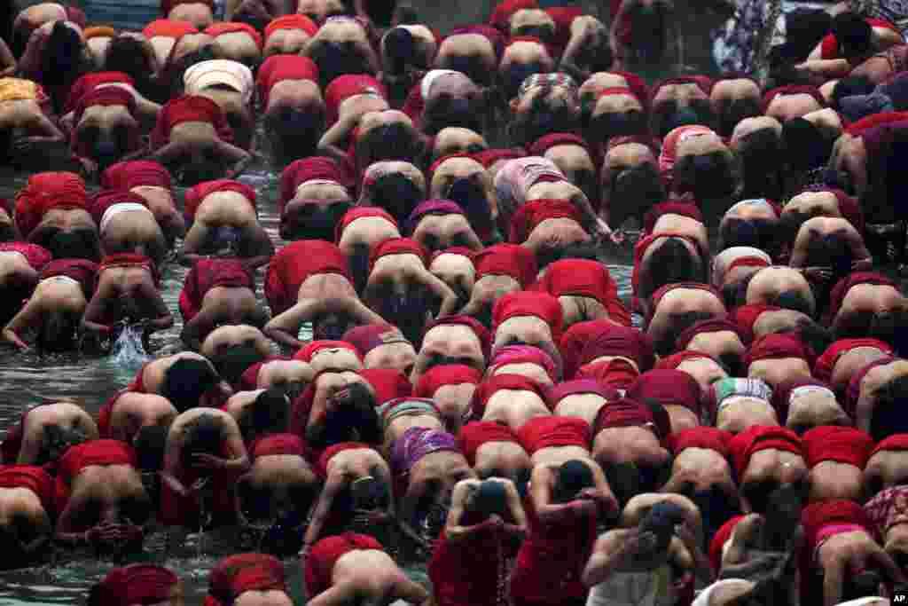 Nepalese Hindu women take holy bath in Bagmati river during Swasthani Bratakatha festival in Kathmandu, Nepal, Monday, Feb. 8, 2016.