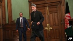 FILE - Afghan President Hamid Karzai leaves a press conference at the presidential palace in Kabul, Afghanistan, Jan. 25, 2014.