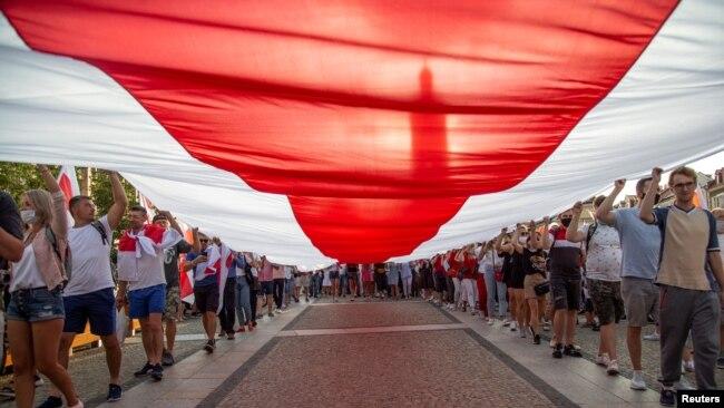 在波兰比亚里斯托克,人们游行举着一面巨大的历史悠久的白俄罗斯国旗表达与白俄罗斯人民团结一致。(2020年8月20日)