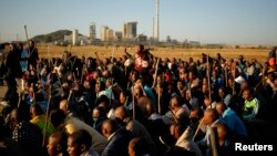 Miners on strike chant slogans as they march in Nkaneng township outside the Lonmin mine in Rustenburg, May 14, 2014.