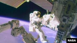 FILE - Astronaut Mike Hopkins works outside the International Space Station during a spacewalk, December 24, 2013, in this still image taken from video courtesy of NASA. Two NASA astronauts floated outside the International Space Station on Tuesday for a second