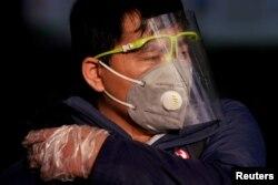 2020年2月12日上海火车站戴着口罩和防护面具的男子。