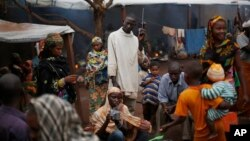 FILE - Muslim refugees listen to a radio at the Catholic church in Carnot, Central African Republic, where they are taking shelter from Christian militants, April 16, 2014.