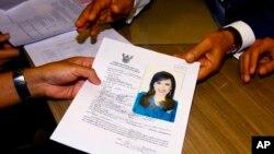 Pemimpin Partai Thai Raksa Chart, Preecha Pholphongpanich (kanan), menyerahkan dokumen dengan foto Putri Ubolratana di Komisi Pemilihan Umum Thailand, di Bangkok, Thailand, Jumat, 8 Februari 2019.