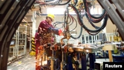 中國山東濰坊的江淮汽車製造廠的工人在生產線上。(2020年2月28日)