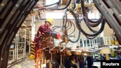 中國山東濰坊的江淮汽車製造廠工人在生產線上。 (2020年2月28日)