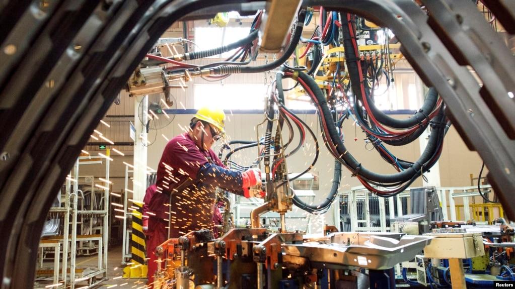 中国山东潍坊的江淮汽车制造厂的工人在生产线上(2020年2月28日)(photo:VOA)