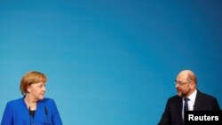 德国保守派联盟领袖默克尔总理(左)和德国社会民主党领袖马丁·舒尔茨在柏林商讨有关组成联合政府的会议后举行记者会。(2018年1月12日)