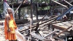 泰柬邊境星期一晚的武裝衝突後﹐一名柬埔寨僧侶看著遭火箭損壞的房舍。