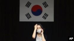 Seorang pekerja di distrik perkantoran Dongdaemun, Seoul, Korea Selatan mengenakan masker untuk tindakan pencegahan penularan virus MERS (Foto: dok).