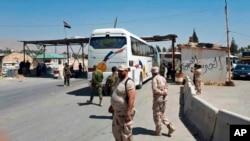 叙利亚政府军士兵看着载有伊斯兰军成员的大客车把人们从被围困城市东古塔撤离。(2018年4月2日)