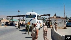 This photo released by the Syrian official news agency SANA, shows Syrian government forces overseeing the evacuation by bus of Army of Islam fighters from the besieged town of Douma, just east of Damascus, Syria, Apr. 2, 2018.