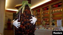 British pastry cook Michael Lewis-Anderson holds a sixty-kilogram giant chocolate egg with candied orange peel in the form of an artichoke at a Wittamer chocolate boutique ahead of the Easter weekend in Brussels, April 3, 2015.