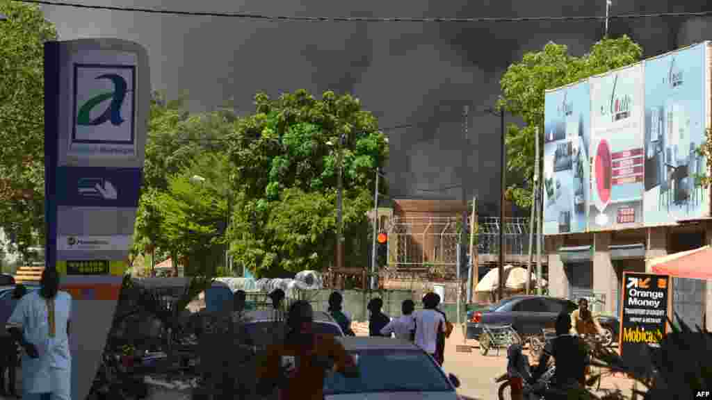 Plusieurs témoins regardent une épaisse colonne de fumée noire au niveau de l'état-major des armées à Ouagadougou, Burkina Faso, le 2 mars 2018.