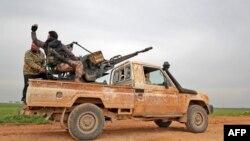 Поддерживаемые Турцией сирийские повстанцы движутся по дороге недалеко от города Тафтаназ на северо-востоке провинции Идлиб, 28 февраля 2020 года.