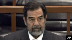 """FILE - In this Dec. 6, 2006 file photo, former Iraq leader Saddam Hussein sits in court in Baghdad, Iraq, during the """"Anfal"""" trial against him."""
