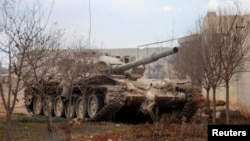 FILE - A Syrian army tank is seen on the outskirts of the northern city of Aleppo, Syria, Feb. 27, 2014. Syrian government troops, backed by Russian forces and Iran-supported Shia militias, are said to be preparing to take the rebel toehold.