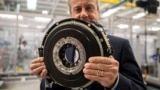 Chris Harris, a CEO of YASA, holds a 24kg (53lbs) axial-flux electric motor for a high-performance electric car as he poses for a photo at the company's headquarters and production facility in Oxford, Britain, August 24, 2021. (REUTERS/May James)