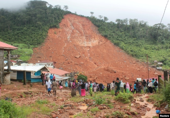 FILE - People inspect the damage after a mudslide in the mountain town of Regent, Sierra Leone, Aug. 14, 2017.
