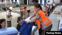지난해 8월 수해 피해를 입은 평안남도 안주시 주민들이 조선적십자회 직원들의 구호품을 분배받고 있다.
