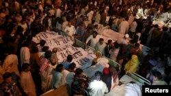 巴基斯坦與印度邊境的哇嘎鎮發生巨大爆炸後,巴基斯坦親屬聚集在死難者旁邊