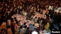 Para anggota keluarga dan kerabat berkumpul di dekat jenazah korban serangan bom di Lahore, Pakistan (2/11).