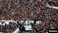 Paus Benediktus XVI, 85 tahun, melambaikan tangan kepada massa dari kendaraan terbuka yang bergerak perlahan melewati lapangan Santo Petrus untuk terakhir kalinya (27/2).