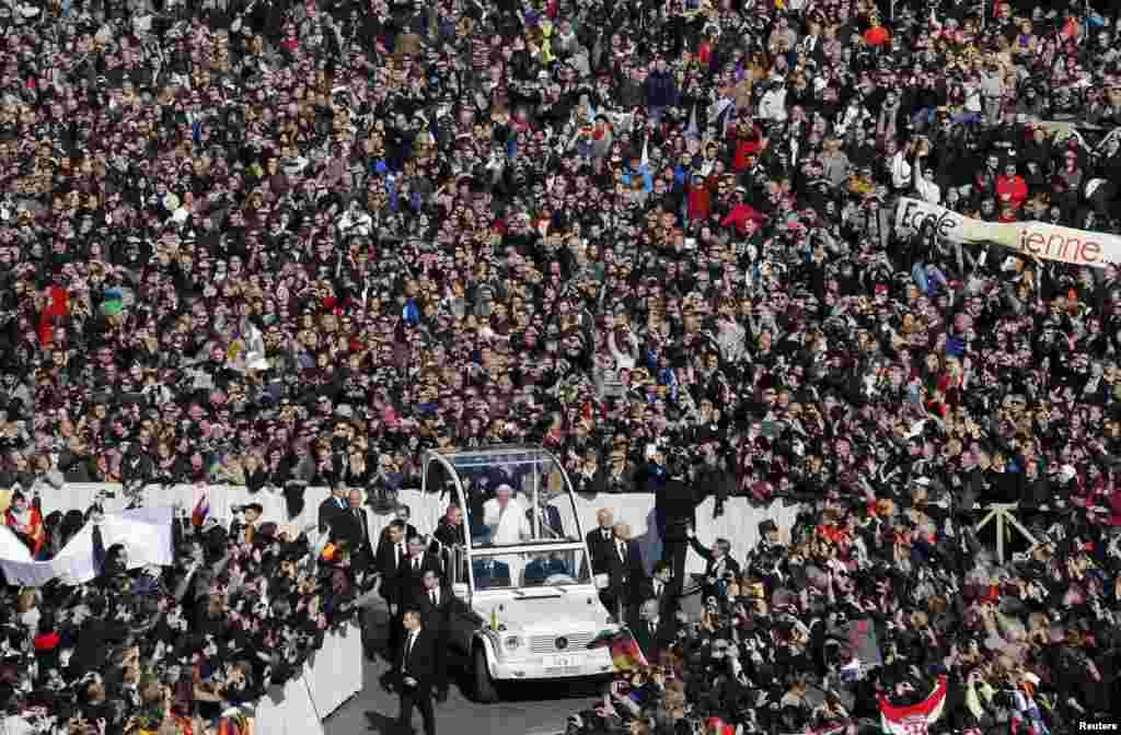 教宗本笃16世搭乘教宗座车通过梵蒂冈挤满信众的圣彼得广场举行最后一次公开接见信众活动的时候,向信众挥手。