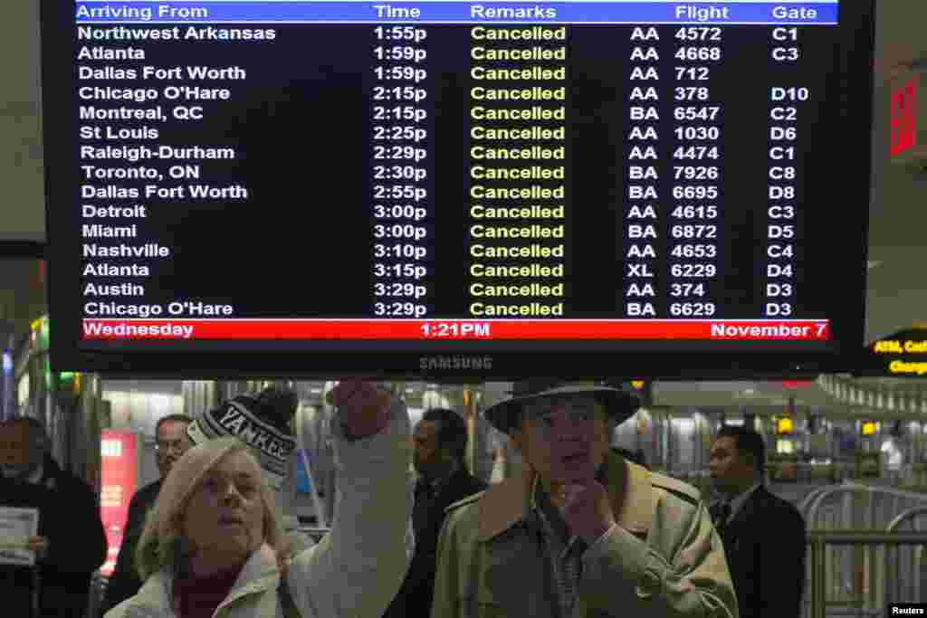 Travelers look at a monitor displaying cancelled flights in New York's LaGuardia airport, November 7, 2012.