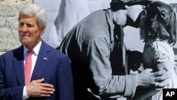 U.S. Secretary of State John Kerry stands near a photo by Tony Vaccaro, whose name graces the town hall of Saint-Briac-sur-Mer, France, June 7, 2014.