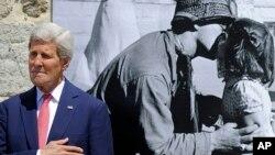جان کری در حال ادای احترام در برابر تالار شهر سن بریاک سور-مر در شمال غربی فرانسه، عکس معروف بوسه آزدی پشت سر اوست - هفتم ژوئن