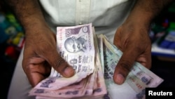 FILE - A private money trader counts Indian rupee currency notes at a shop in Mumbai, India.
