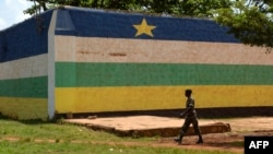 """FILE - A man walks in front of the jail of Bangui, """"Maison Centrale de Ngaragba,"""" whose walls are painted with the colors of the flag of Central African Republic, April 22, 2014."""