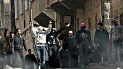 آرشیو: مخالفان دولت سوریه انگشتان خود را به علامت پیروزی تکان می دهند