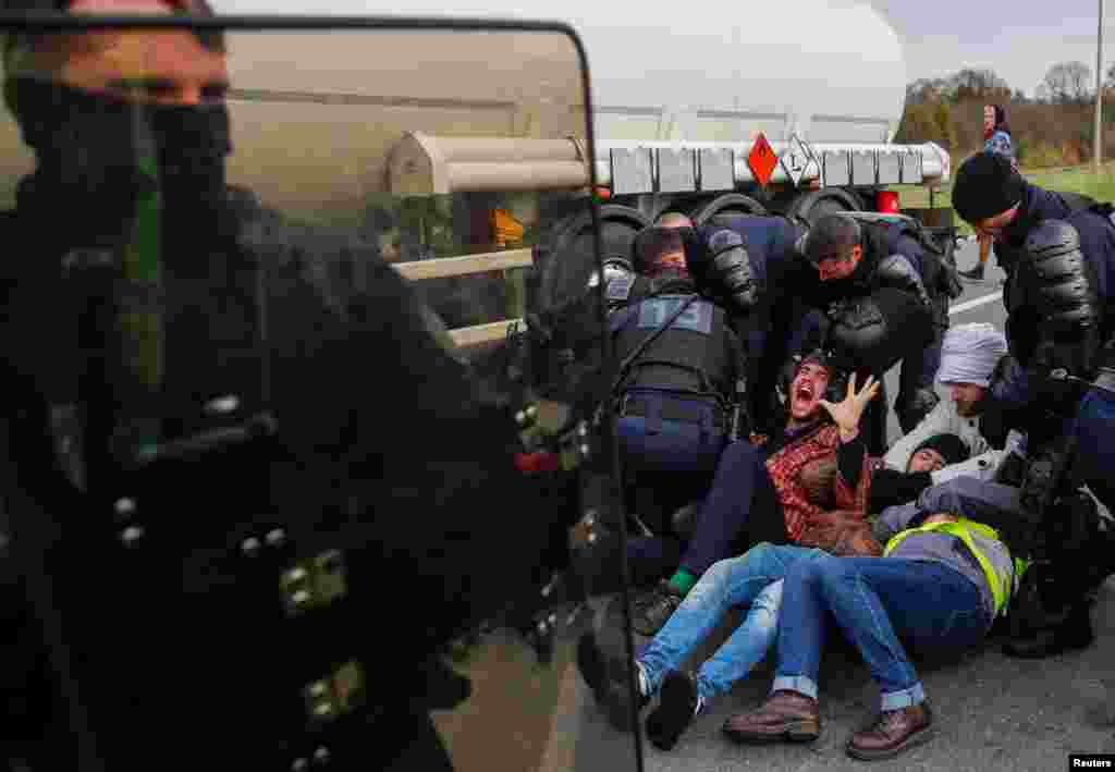 French gendarmes evacuate demonstrators who sit on the road and block full tanker trucks in front of the French oil giant Total refinery in Donges.
