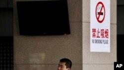 一名中国男子在北京一处明令禁止吸烟的公车站吸烟