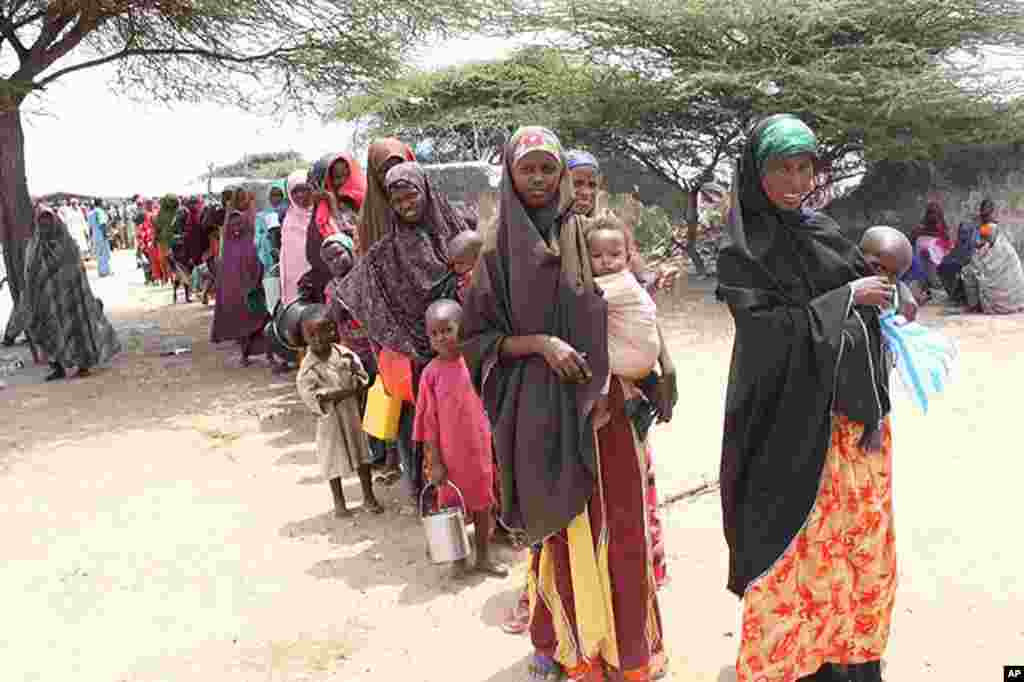 Women stand in line with pots to collect rice at Badbaado IDP camp in Mogadishu, Somalia, August 11, 2011. (VOA - P. Heinlein)