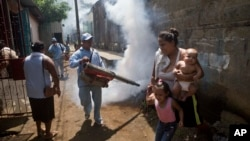FILE - A woman with her children moves out of the way as a health ministry worker fumigates against mosquitoes that transmit dengue fever as well as Chikungunya fever, in Managua, Nicaragua, Oct. 27, 2014.