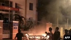 Picture taken on June 10, 2018 shows protesters burning motorcycles in front of a provincial office in Vietnam's south central coast Binh Thuan province in response to legislation on three special economic zones that would grant 99-year leases.