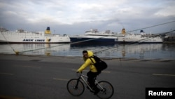 A man rides his bicycle at the port of Piraeus, near Athens, Greece, Feb. 4, 2016. Greek dockworkers began a two-day strike on Feb. 16, 2016, to protest against the sale of the country's two biggest ports, which Athens has promised to international lenders, disrupting operations at cargo terminals.