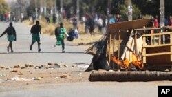Schoolchildren run past a burning barricade, following a job boycott called via social media platforms, in Harare, Wednesday, July,6, 2016. (AP Photo/Tsvangirayi Mukwazhi)