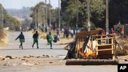 FILE: Schoolchildren run past a burning barricade, following a job boycott called via social media platforms, in Harare, Wednesday, July,6, 2016.