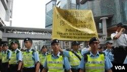 香港警方高舉標語,警告參與學民思潮平反六四遊行的人士,可能被刑事檢控 (美國之音特約記者湯惠芸拍攝)