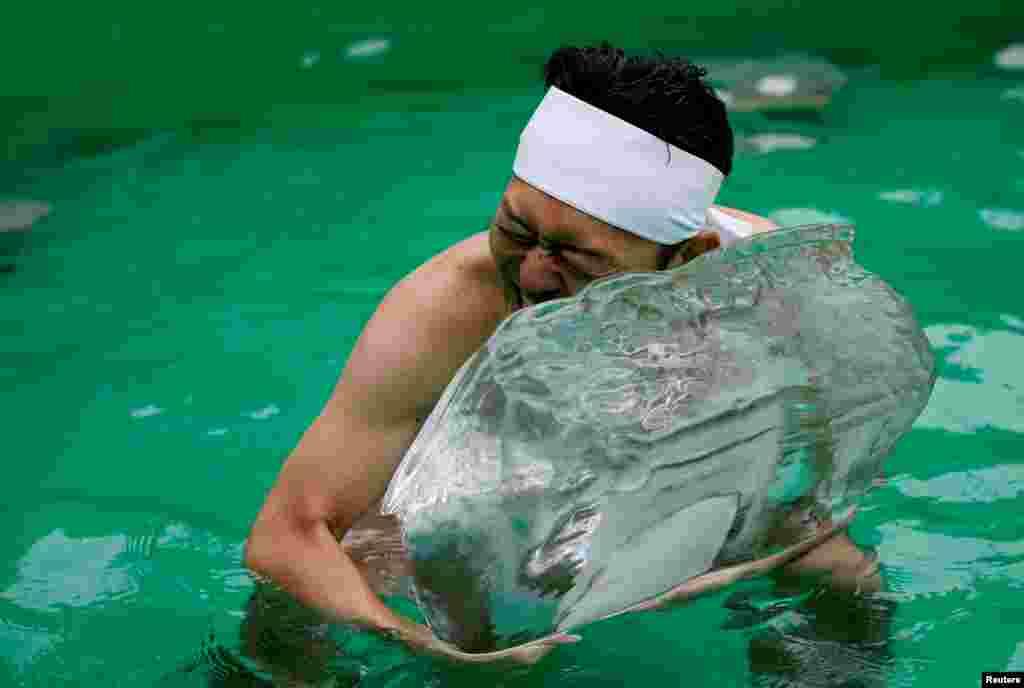 ٹھنڈے پانی میں غسل کے بعد ایک شخص برف کی سل سے لپٹا ہوا ہے۔ یہ ٹوکیو کے ٹیپوزو ابساری نام سے مشہور ایک درگاہ میں ہر سال منعقد ہوتی ہے۔