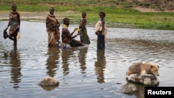 FILE - A Turkana woman and children bathe in a hot spring pool in northwestern Kenya inside the Turkana region of the Ilemy Triangle, Sept. 26, 2014.