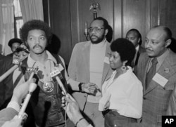 Jesse Jackson speaks to reporters at the Operation PUSH Soul Picnic in New York, March 26, 1972, as Tom Todd, vice president of PUSH, from second left, Aretha Franklin and Louis Stokes look on.